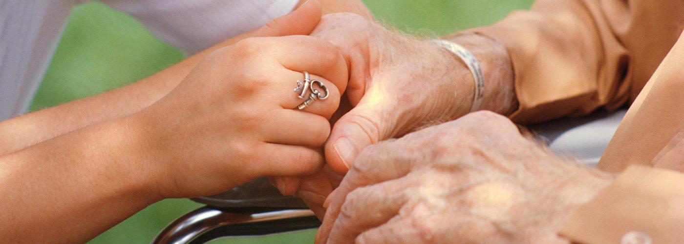 caregiver and elderly holding hands