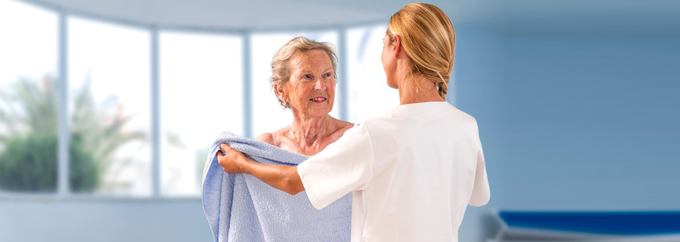 caregiver handing out the senior woman towel - Orchard House