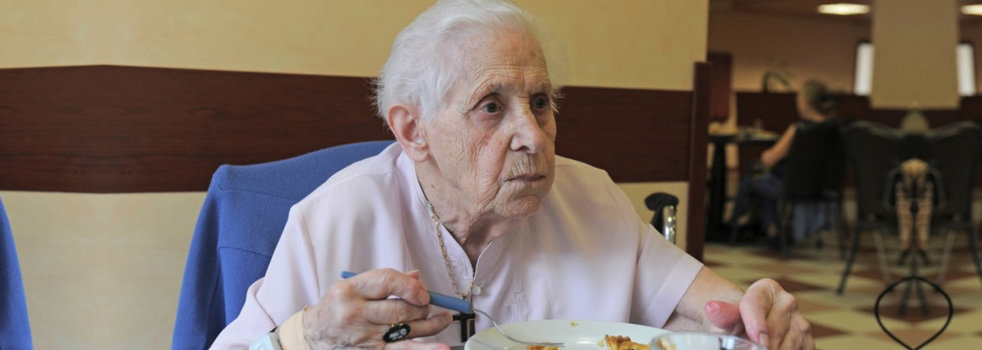 senior woman smiling and eating in a retirement facility - Orchard House